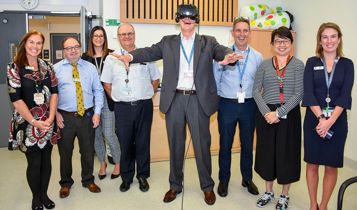 man stands with hospital staff in a corridor wearing virtual reality goggles